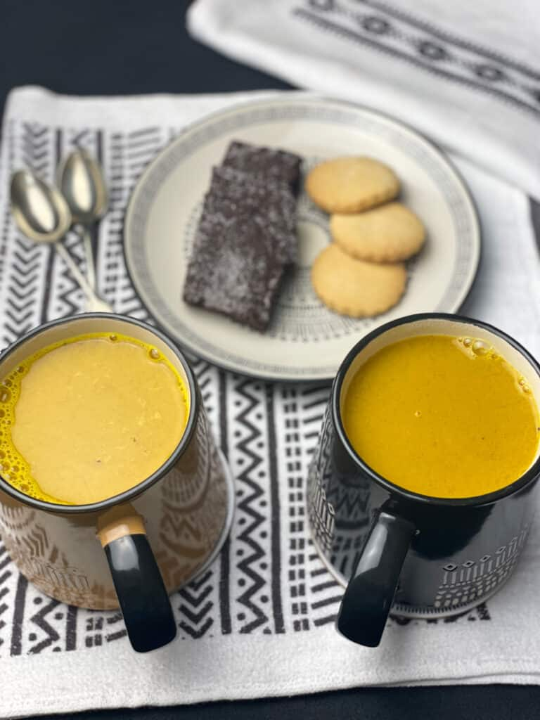 turmeric latte poured into 2 mugs, plate of cookies in front and 2 spoons, all on black and white pattern tea towel.