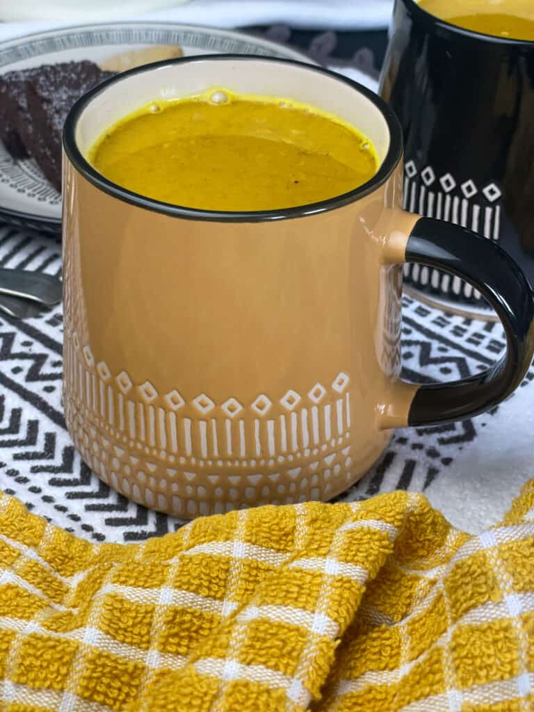 turmeric latte served in large yellow mug with white pattern, yellow check tea towel and black and white tea towel.