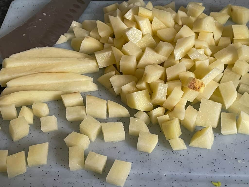 white potatoes chopped into cubes on a white chopping board.