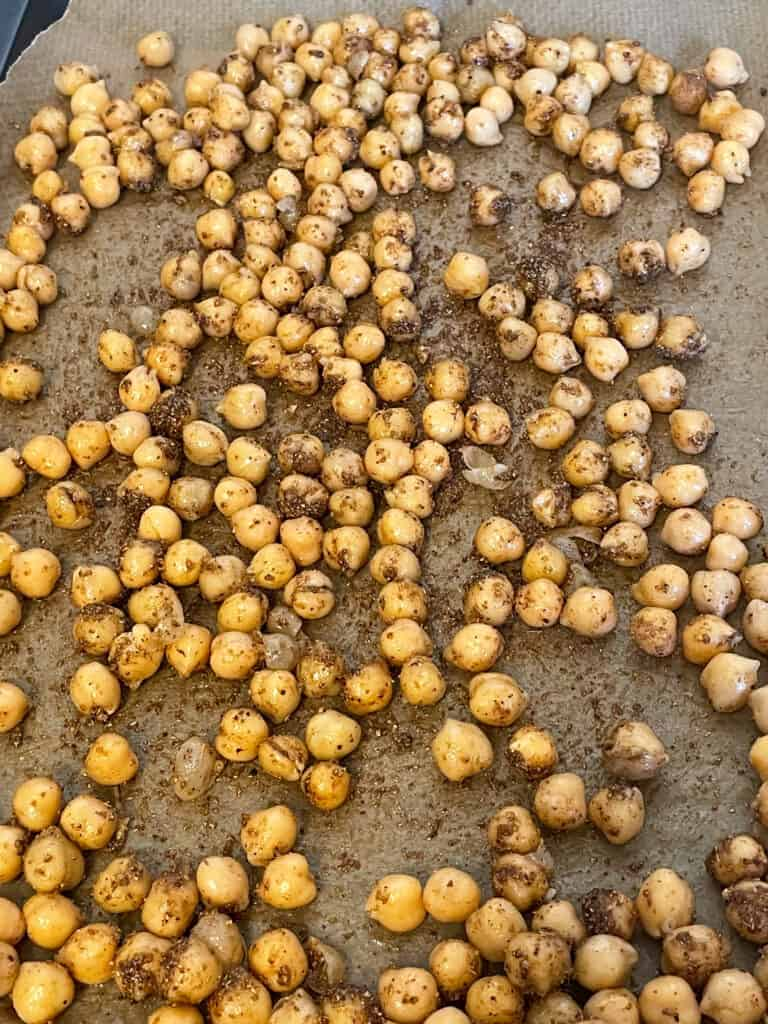 Chickpeas mixed with spices and placed on baking tray.