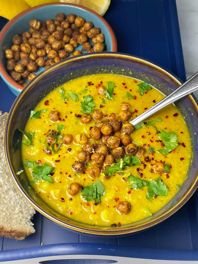 bowl of curried cauliflower soup in blue bowl, slices of bread to side, roast chickpeas above, silver spoon and all sitting on blue tray.