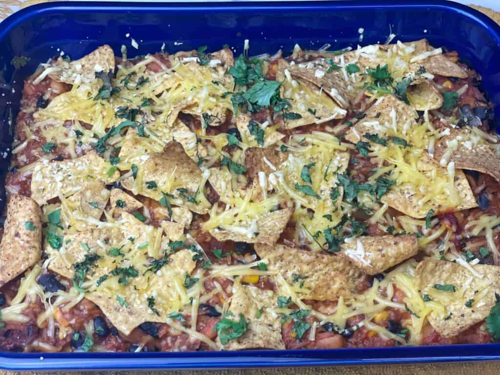 casserole placed in a baking dish, tortilla chips scattered on top with grated vegan cheese, and chopped coriander.