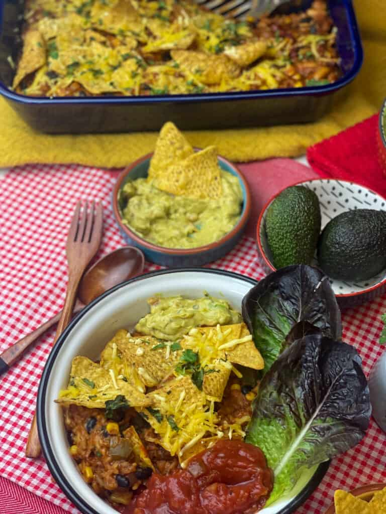 casserole served in bowl with salsa, guacamole and red lettuce leaves, small bowl of guacamole and avocados to side, and blue casserole dish in background, red and white check tablecloth and wooden fork.