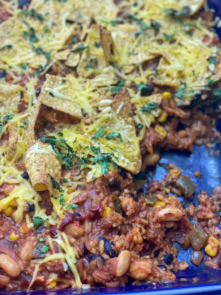 mexican bean and rice casserole in blue casserole dish, with a few servings removed.