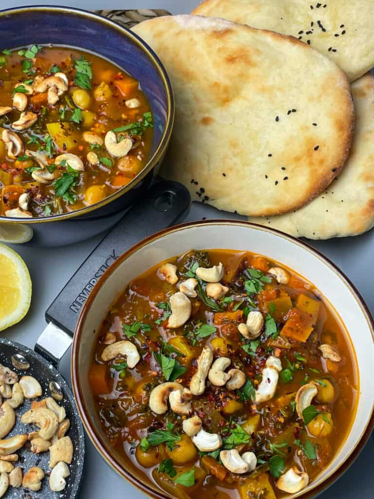 Two bowls of chickpea soup with small pan of cashews, lemon wedge to side, naan breads, all placed on grey tray.