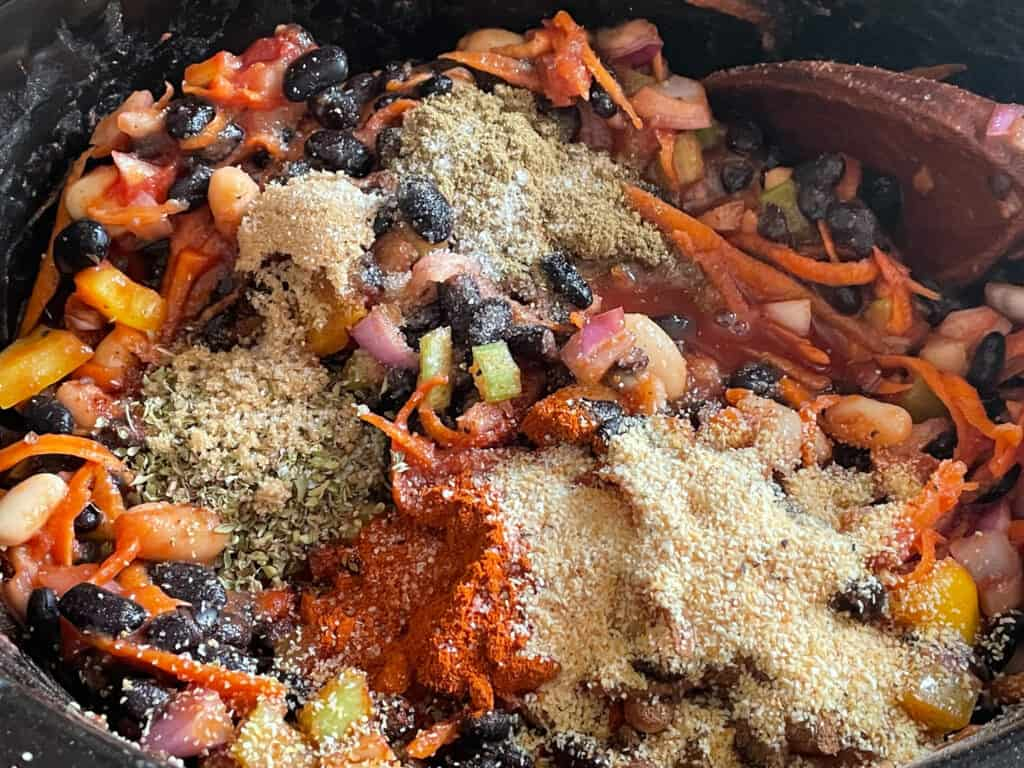 various spices and herbs added to slow cooker with the veggies and beans.