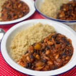 three bowls of black bean chilli with quinoa sitting on red check tea towel.