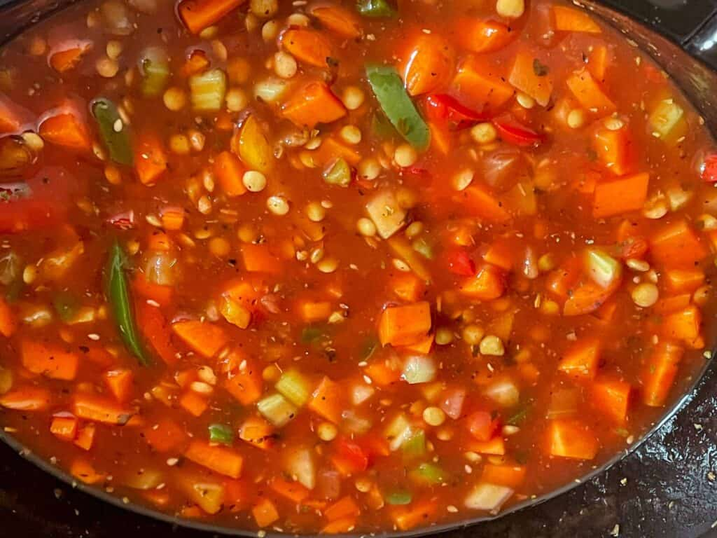 Flavourings and vegan stock mixed through lentils and veggies in the slow cooker.
