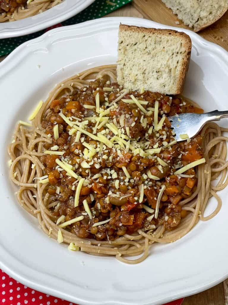Bolognese served with grated vegan cheese and a small wedge of herb bread in white bowl with silver fork to side.