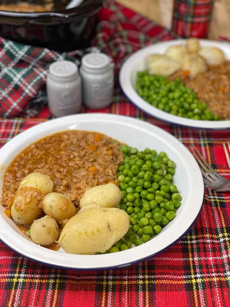 Two white plates with vegan mince and tatties, peas, red tartan cloth underneath, blue salt and pepper shakers at the top, silver fork to side.