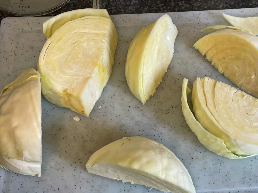 White cabbage sliced into large wedges on chopping board.
