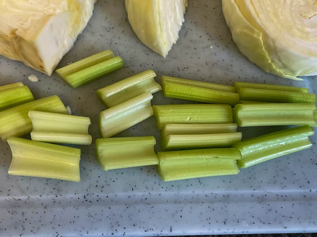 Celery sliced into large pieces beside cabbage wedges.