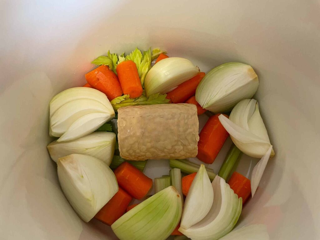 Tempeh nestled in a stock pot with onion wedges, carrot slices, celery stalks.