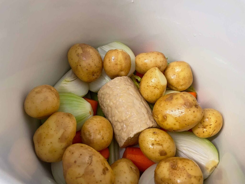 Whole potatoes added to stew in stock pot.