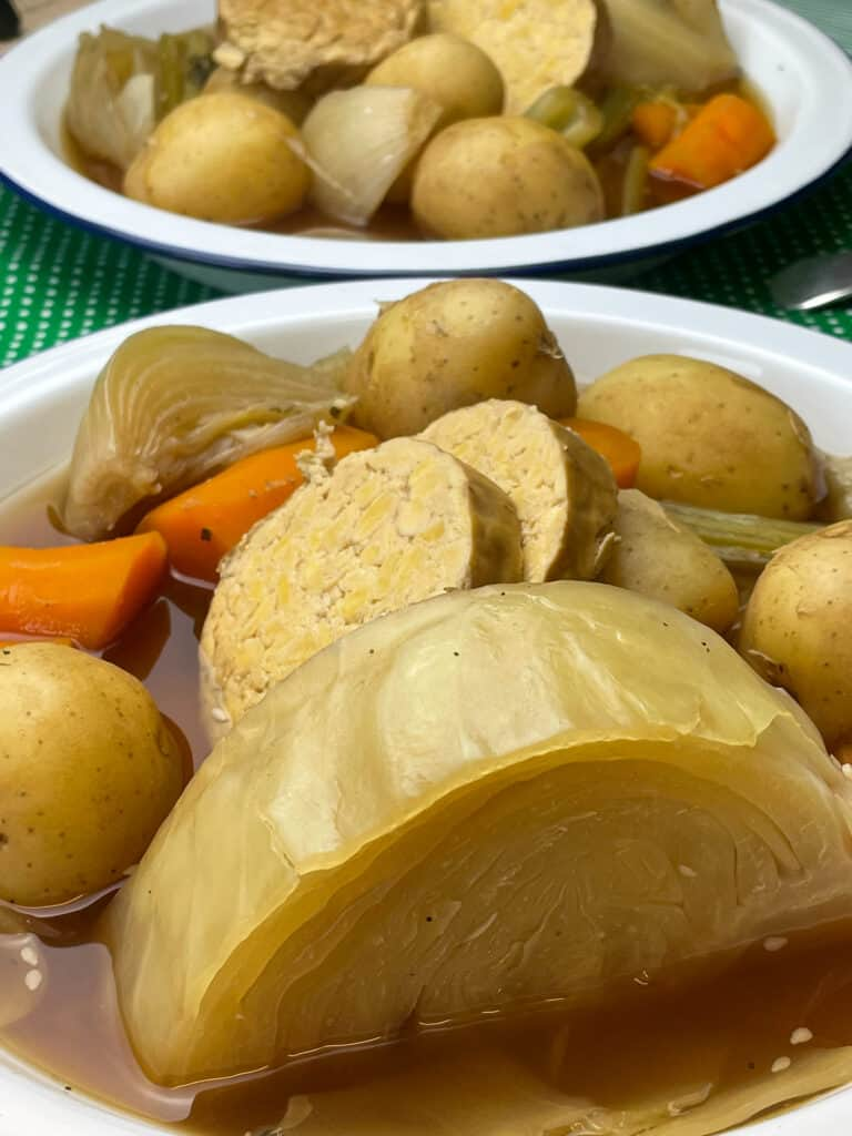 Close up of bowl of stew with large cabbage wedge to front, second bowl of stew in background.