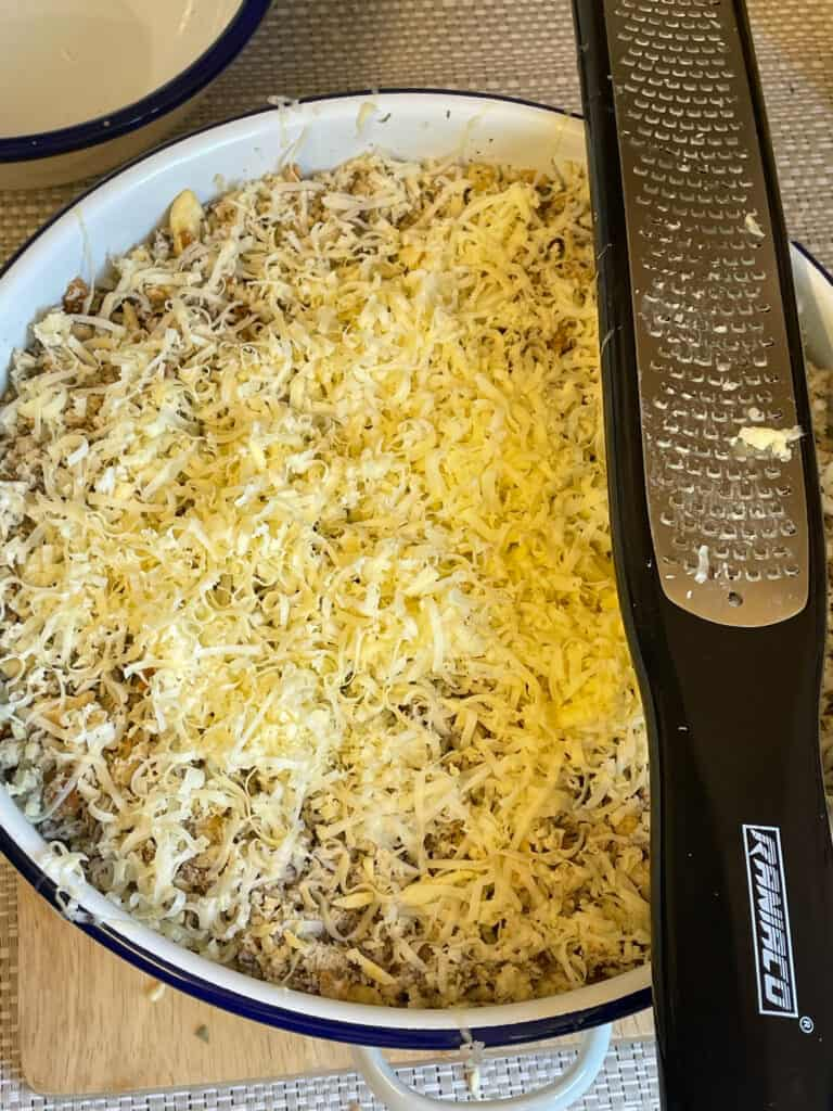 Grated vegan cheese over the green bean casserole, grater to side.