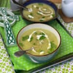 Two bowls of oatmeal leek broth on tray, with green flower tea towel, green and white celtic cross to side, white jug of cream to side, shamrock background.
