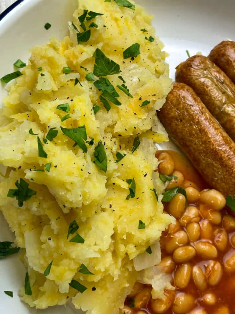 wartime champ with chopped parsley, baked beans and sausages at the side of the white plate.