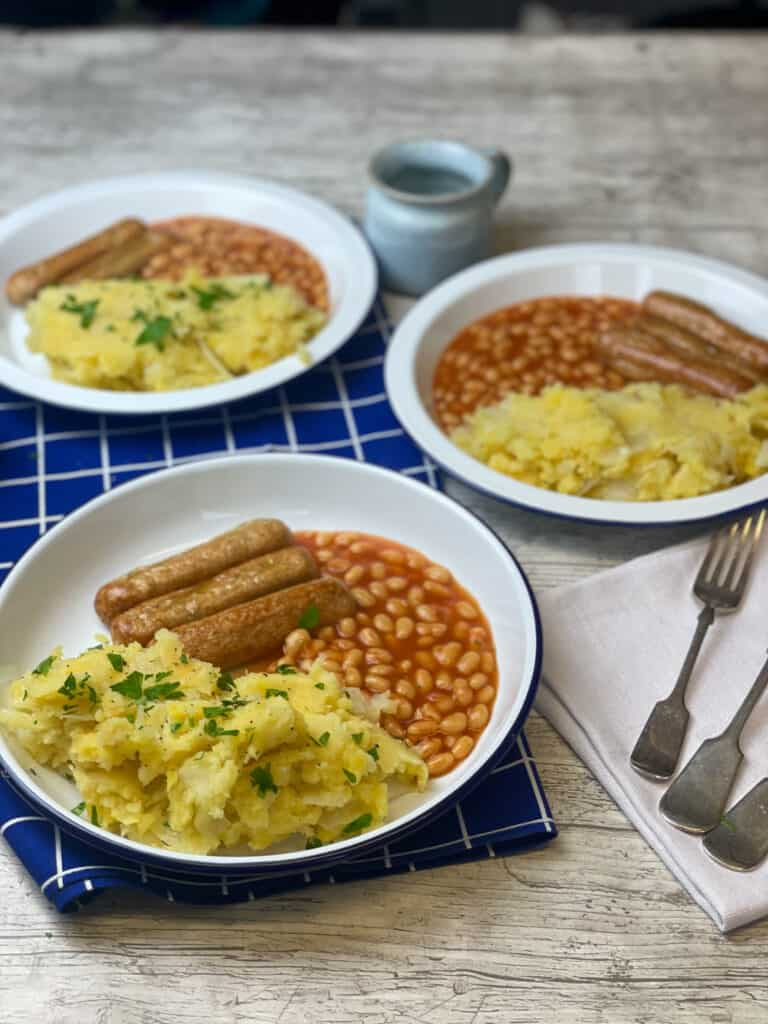 3 servings of wartime champ served with baked beans and vegan sausages on white enamel plate, silver forks to side, and small blue cup.