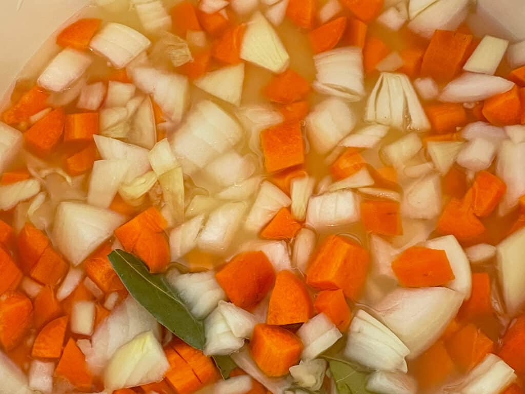 carrot, onion and bay leaf added to soup pan.