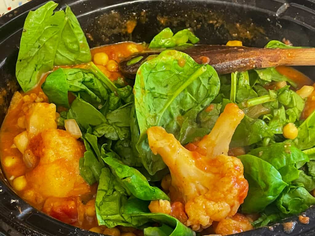 Fresh spinach added to the tikka masala in the slow cooker.
