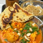 Cauliflower tikka masala in small silver curry bowl, with naan bread at side, small silver curry dish with brown rice, small brown cup to side.