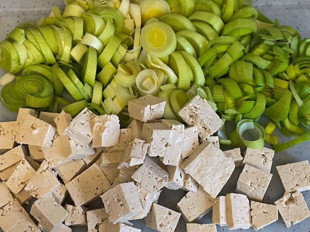 Sliced leeks and chopped tofu on chopping board.