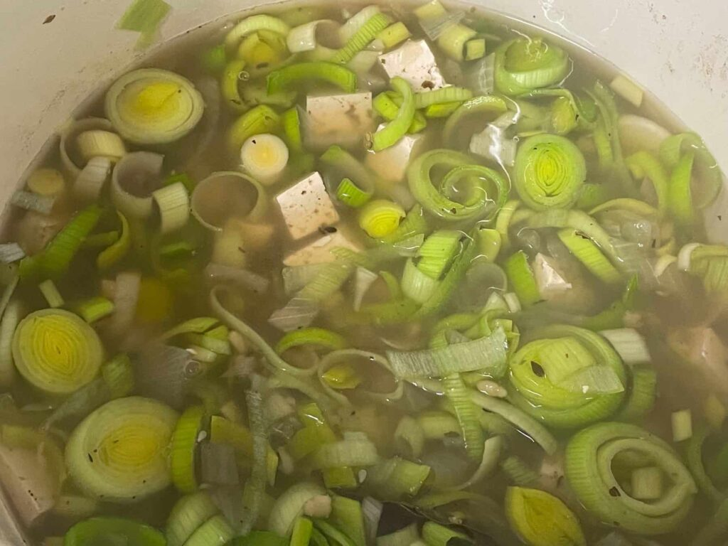 Leeks and tofu added to the soup pan.