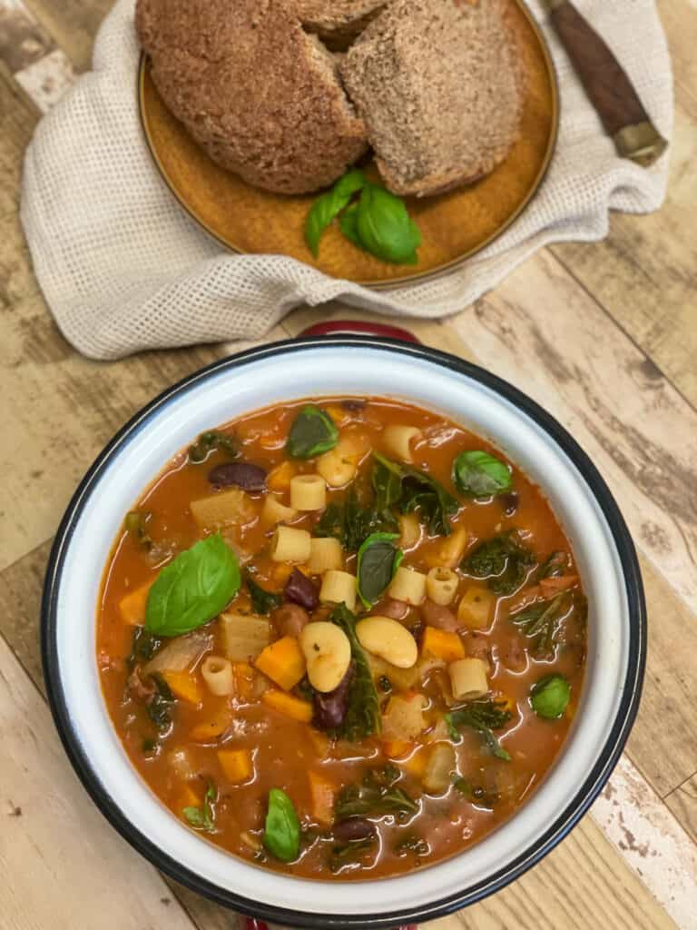 Bowl of Minestrone soup with brown wood plate with crusty bread, light brown wood background.