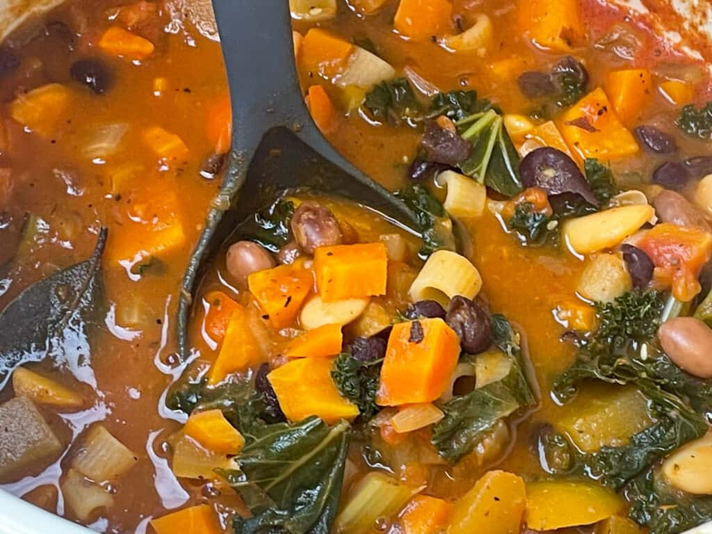 Ladle in cooked Minestrone soup ready to serve.