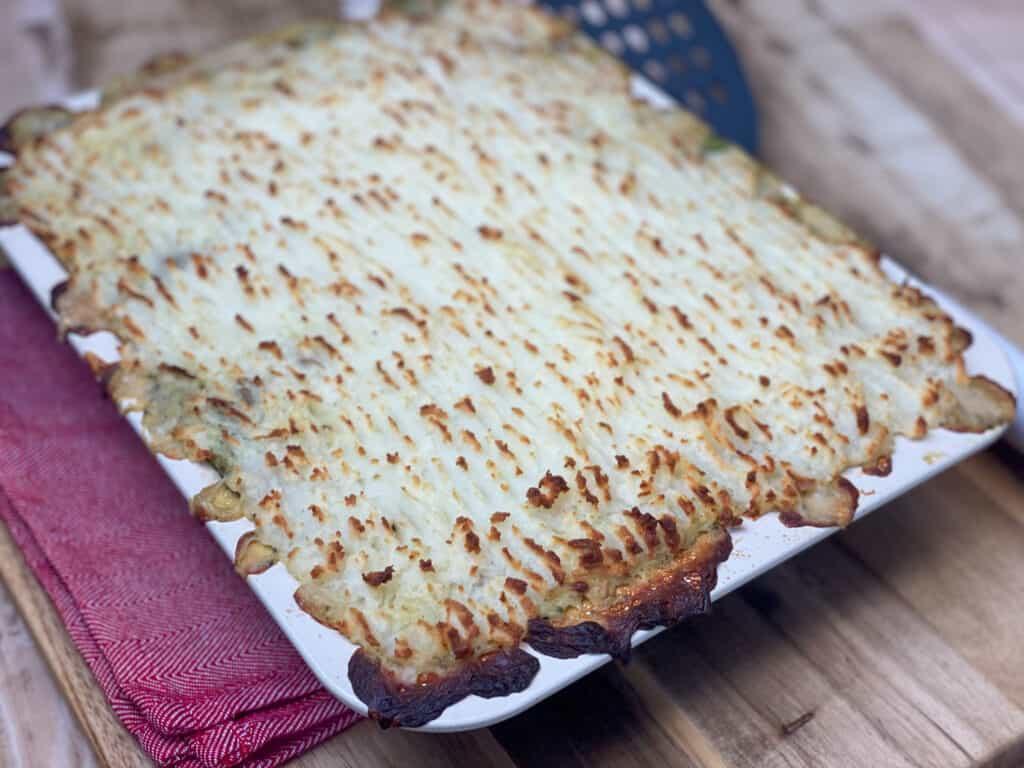 Vegan vegetable hotpot baked golden and crispy, sitting on red tea towel on wooden board.