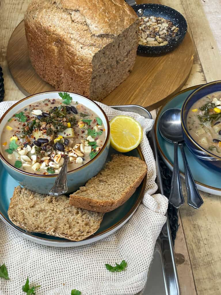 A green bowl of spicy peanut soup served with wholemeal bread, lemon wedge, second bowl to side, loaf of wholemeal bread above on bread board.