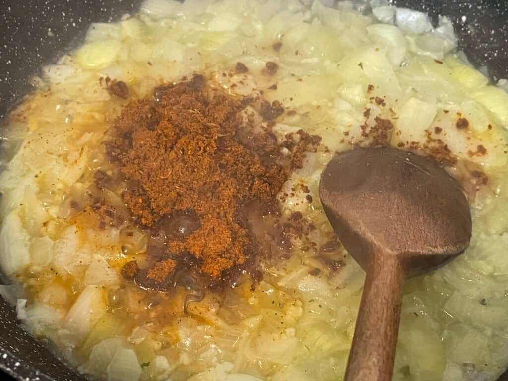 BBQ spice mix added to cooked onions, with wooden spoon.