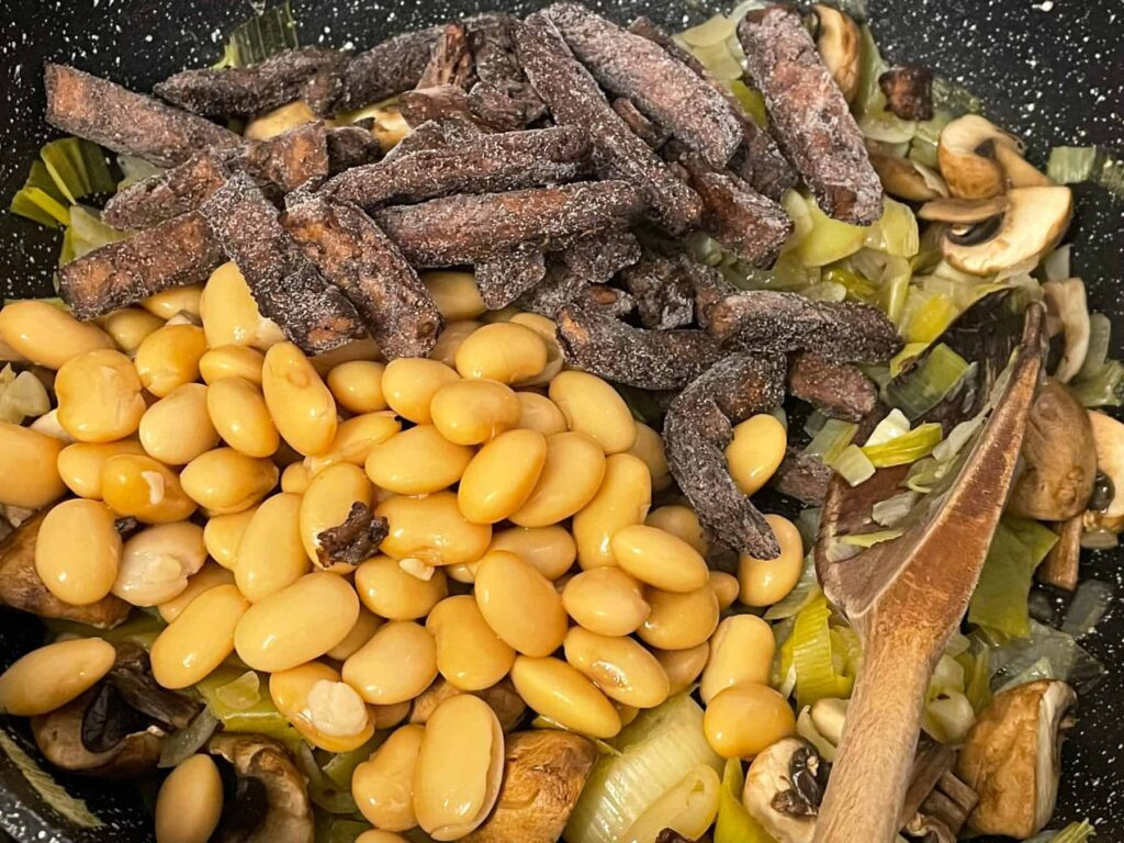 Butterbeans and meat-free beef strips added to mushrooms in skillet.