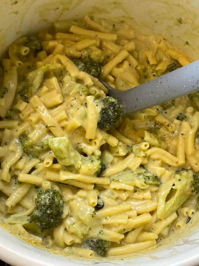 Cheesy pasta ready to serve with grey ladle.