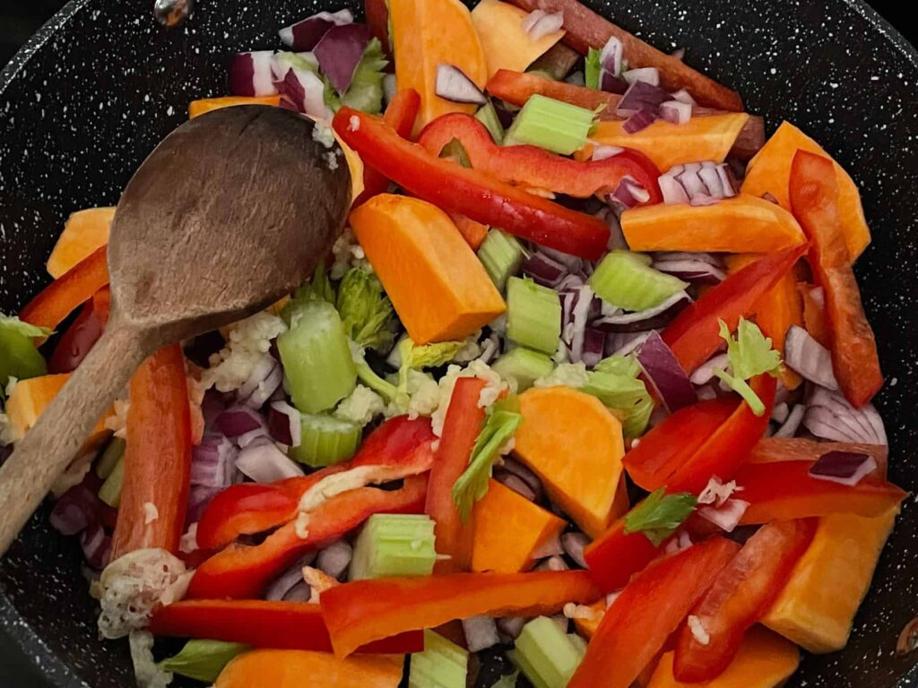 Sausage casserole veggies in skillet pan with wooden spoon.