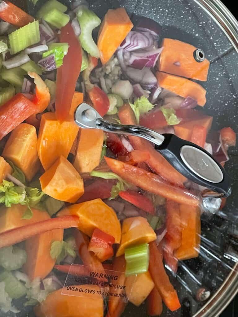 Lid on skillet pan cooking the veggies.