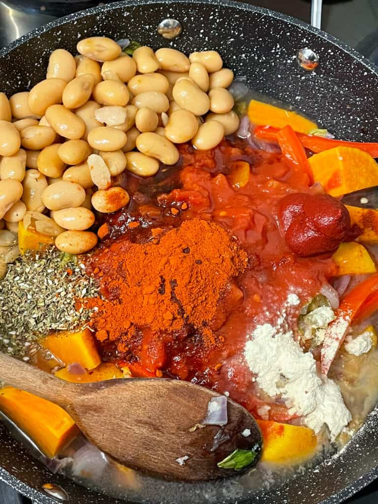 Flavourings added to the veggies in skillet, including butterbeans and chopped tomatoes.