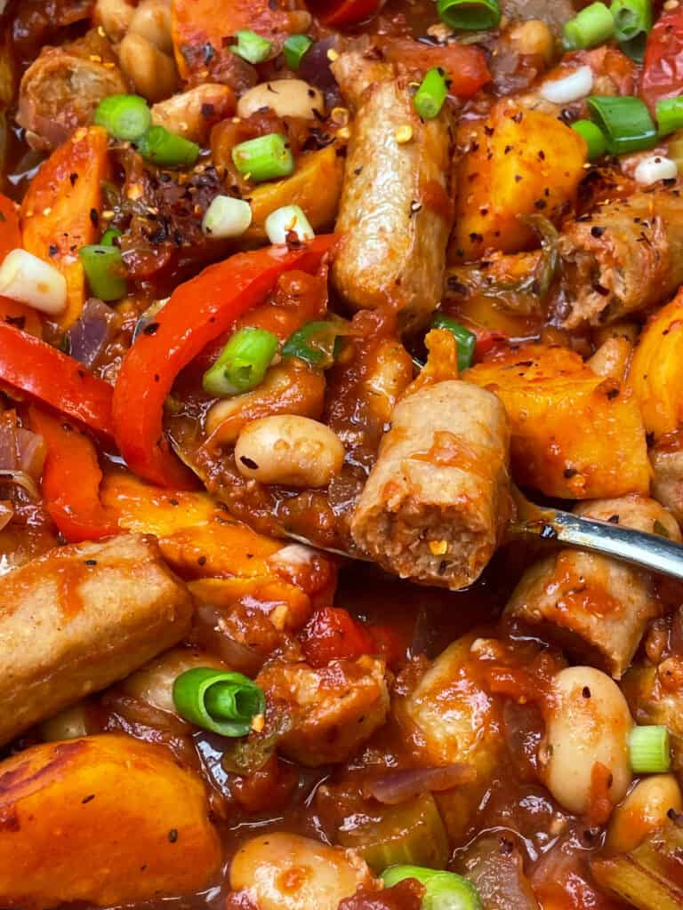 meat-free sausages halved in two and mixed through the casserole, silver spoon in the casserole.