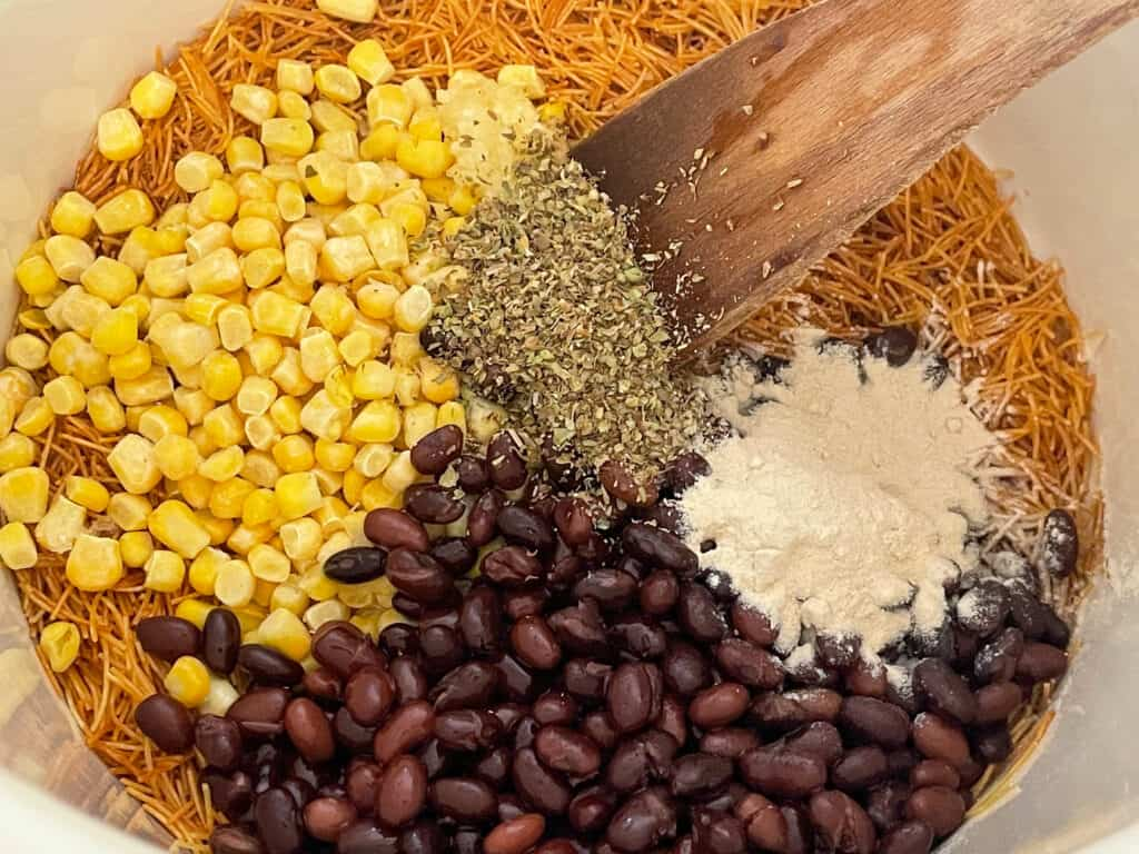 Black beans, corn, onion powder and dried herbs added to golden short pasta in soup pan