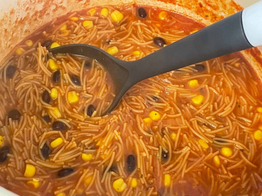 Mexican bean soup with black beans and corn cooked and ready to serve in soup pan with grey ladle.