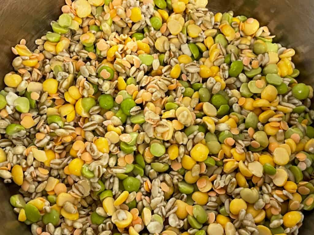 Soup or broth mix, made up with barley, split peas and red lentils all in silver soup pan.