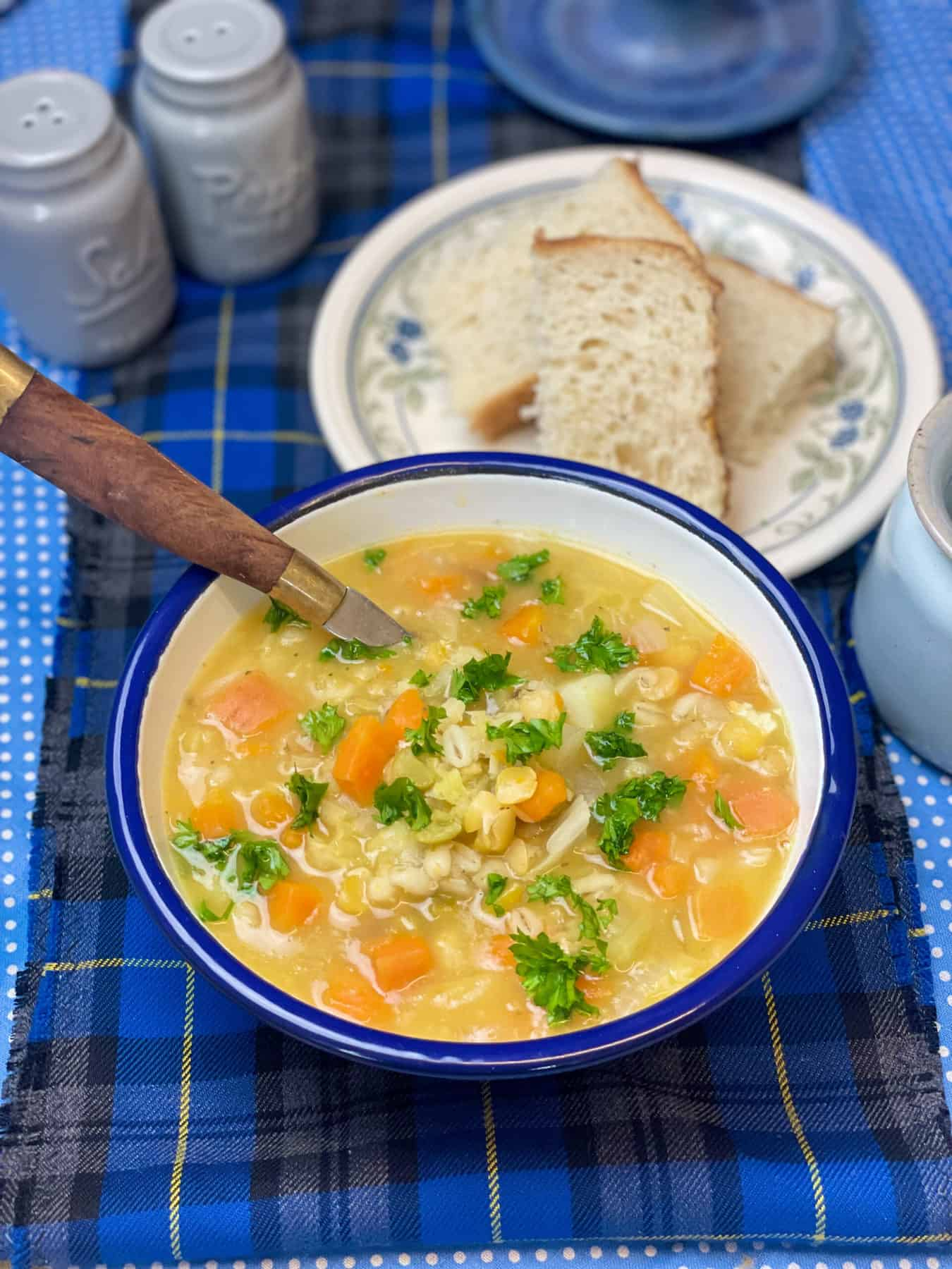 Soup served with crusty bread and chopped parsley, blue tartan background.