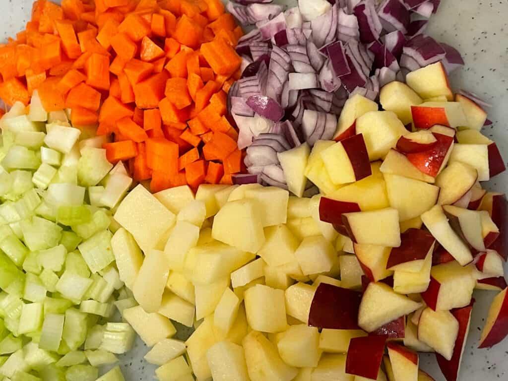 Vegan Mulligatawny soup veggies diced on a white chopping board.