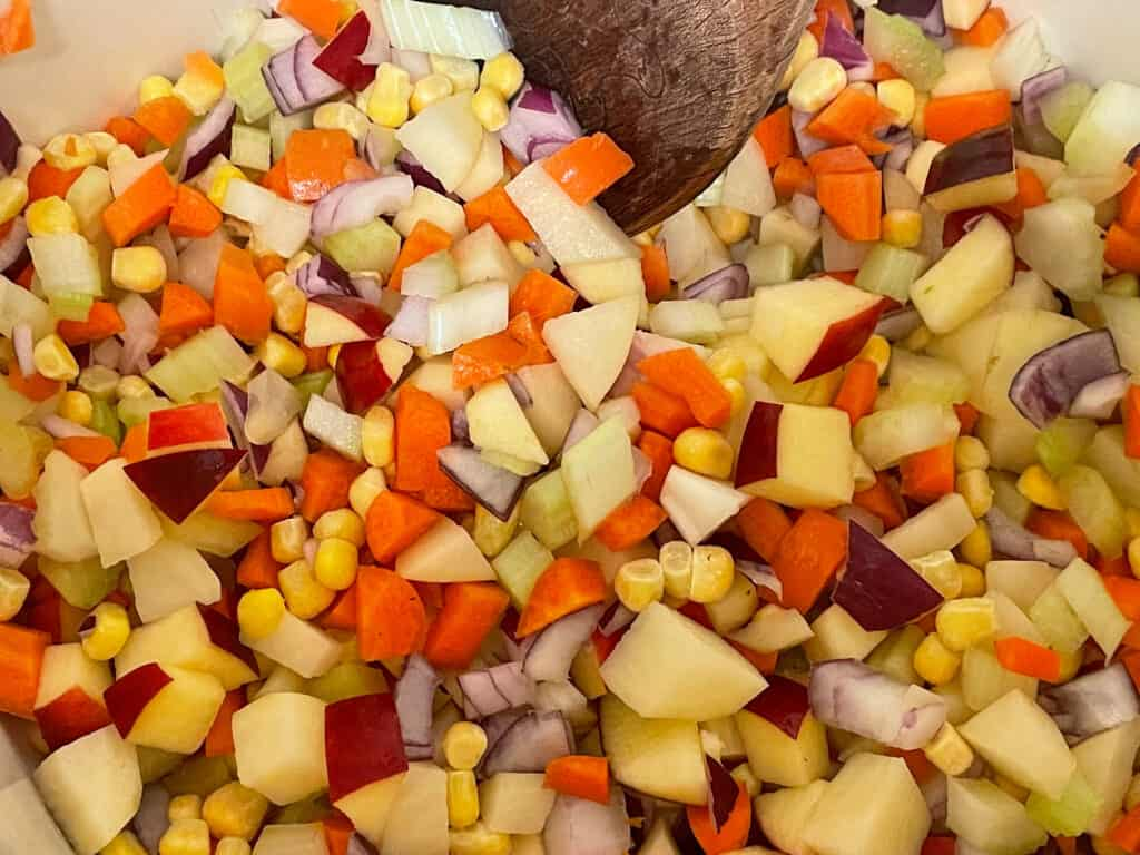 Diced veggies and veggie stock in soup pan.