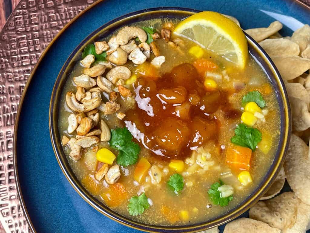 Vegan Mulligatawny soup served in blue bowl, close up with mini poppadum's, and lemon wedge.