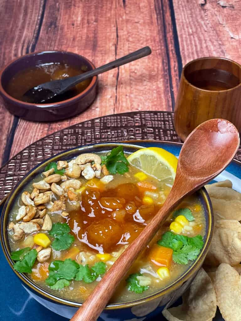 Blue bowl of vegan curried Mulligatawny soup with wooden spoon, wooden cup, small dish of mango chutney and brown wood background.