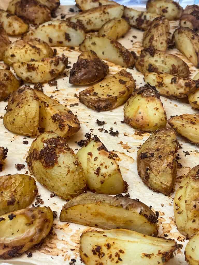 Potato wedges roasted on baking tray.
