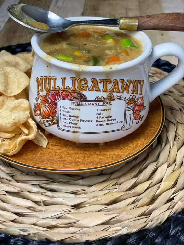 A soup mug full of fruity curried soup, with the word Mulligatawny written on the mug with illustrations and recipe, served on wooden plate with mini poppadum's and wicker mat.