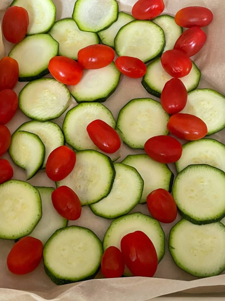 Slices of courgette/zucchini and cherry tomatoes on a baking pan.